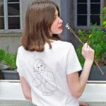 femme tenant une fleur de dos, elle porte un tshirt blanc en coton bio de la marque leonor roversi