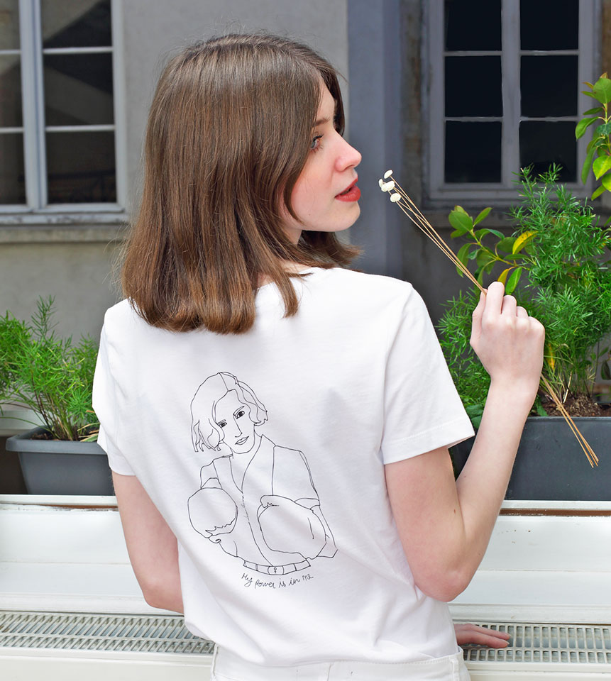 femme tenant une fleur elle porte un t-shirt blanc freyja de la marque leonor roversi