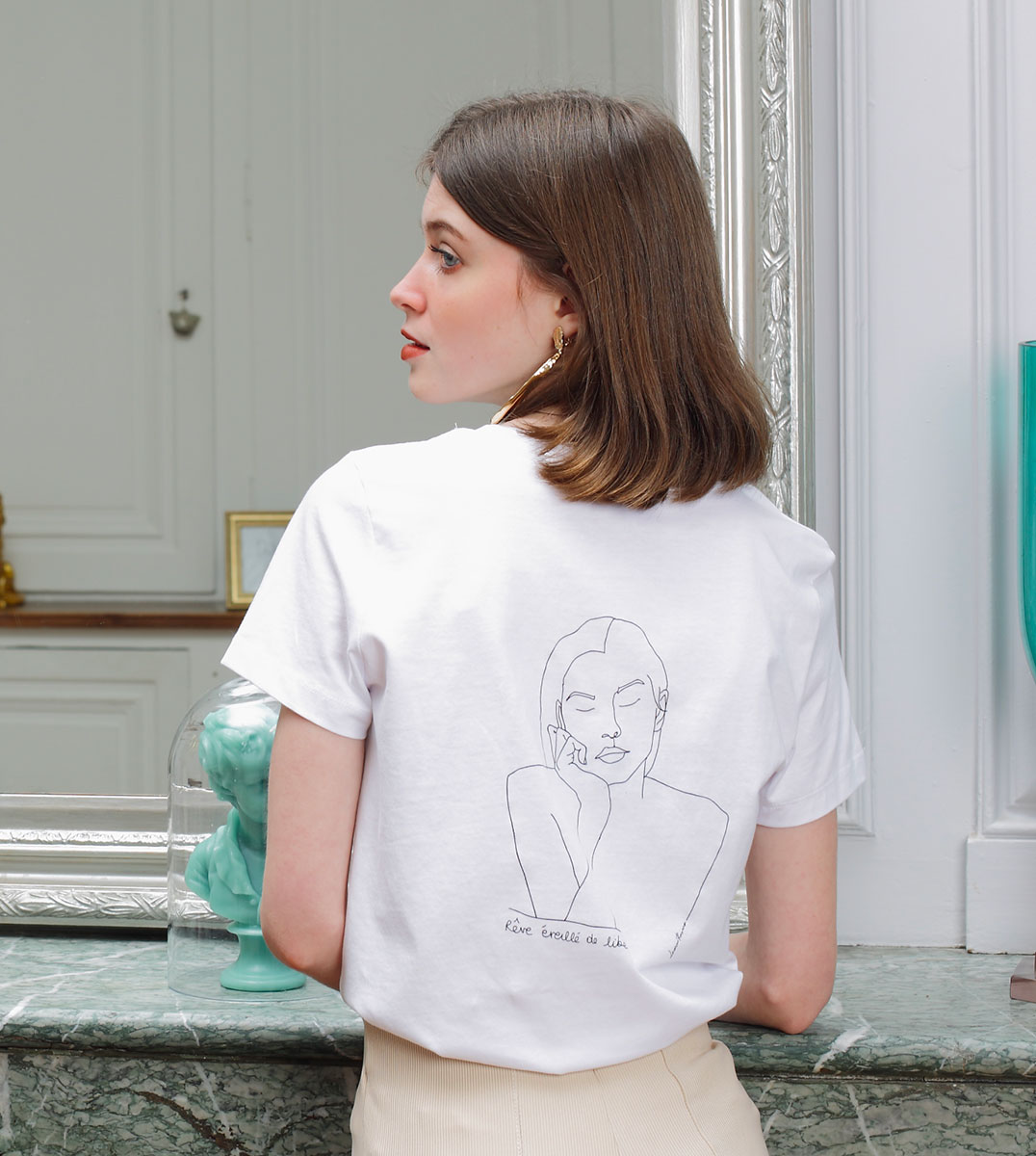 femme de dos portant un tshirt blanc en coton bio, sur le dos du tshirt themis