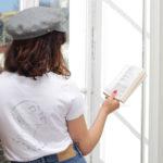 femme de dos qui lit un livre, elle porte un tshirt blanc en coton bio de la marque leonor roversi