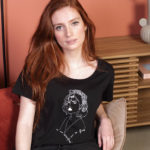 Une femme rousse porte un tshirt noir lupita leonor roversi. Elle est assise sur un fauteuil et regarde l'objectif