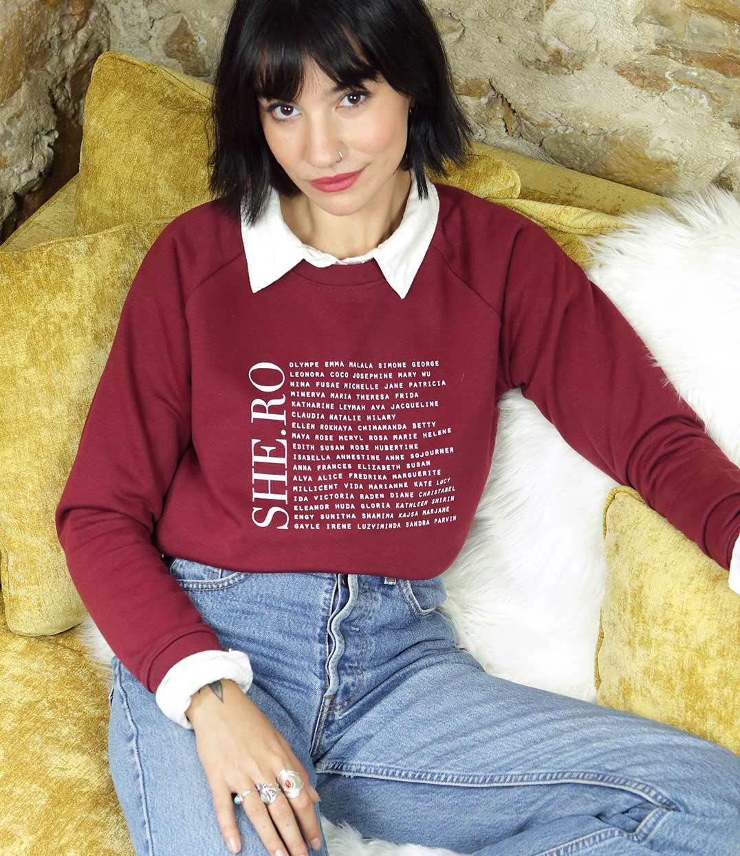 femme assise sur camapé portant un sweatshirt bordeaux avec ecritures feministe leonor roversi