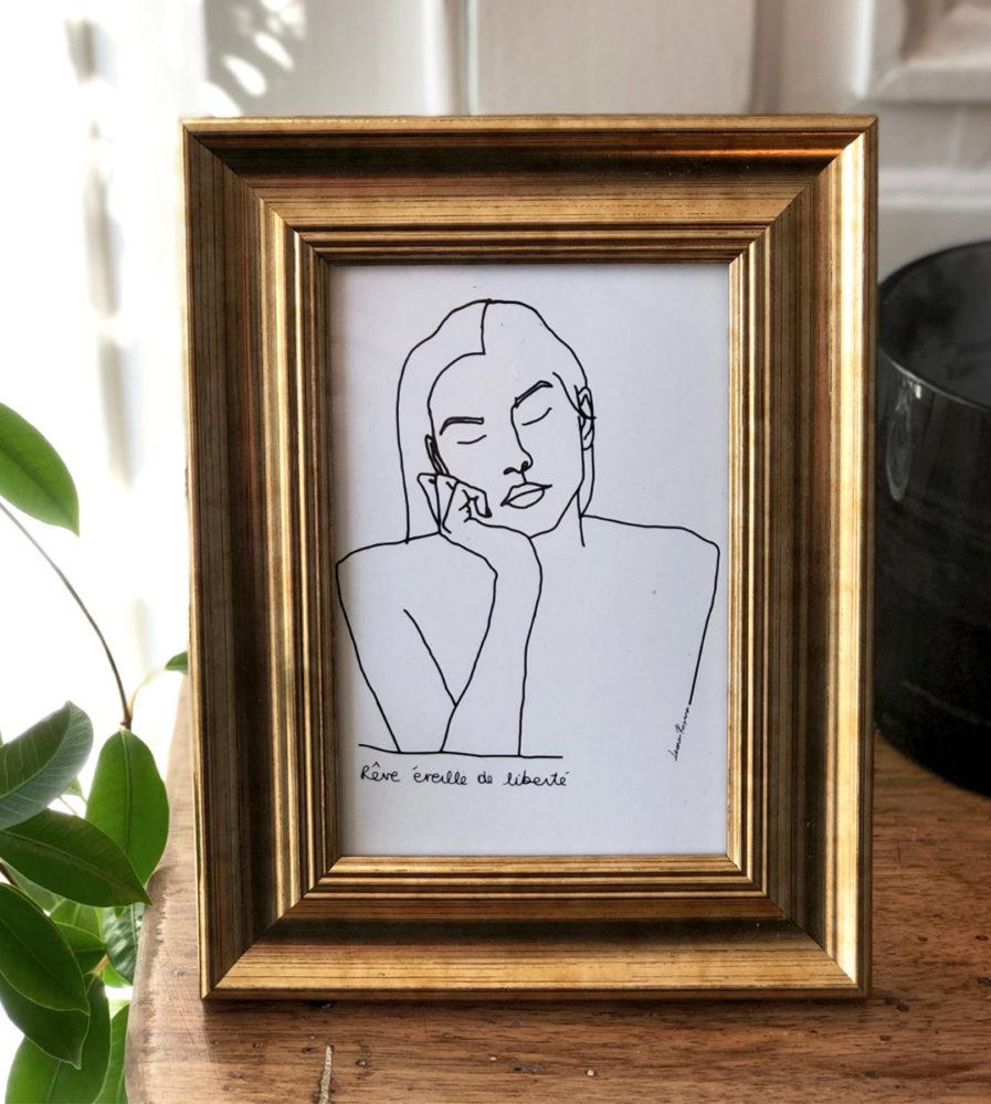 Image d'un cadre doré avec une carte postale d'un visuel d'une femme qui rêve, Themis