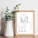 Image d'un cadre avec l'affiche A4 d'une femme qui rêve, Themis, à côté d'un pot avec des eucalyptus artificiels