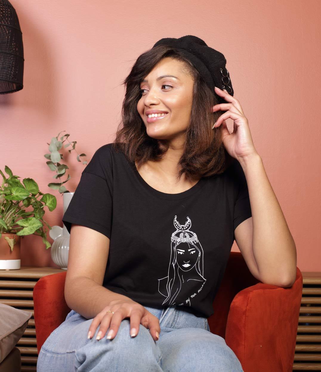 femme assise sur un fauteuil qui porte le t-shirt coyoqui noir loose