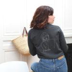 Femme de dos assise, portant le sweatshirt gris en coton bio, Thémis, Leonor Roversi