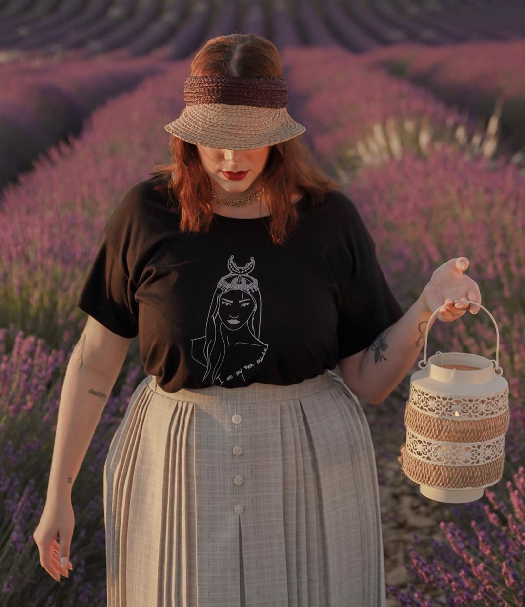femme qui porte un t-shirt noir loose coyoqui dans un champ de lavande