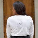 femme posant de dos, elle porte un sweatshirt qui représente la déesse nordique freyja, de la marque leonor roversi