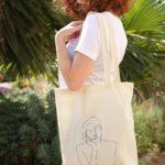 femme portant tote bag déesse thémis