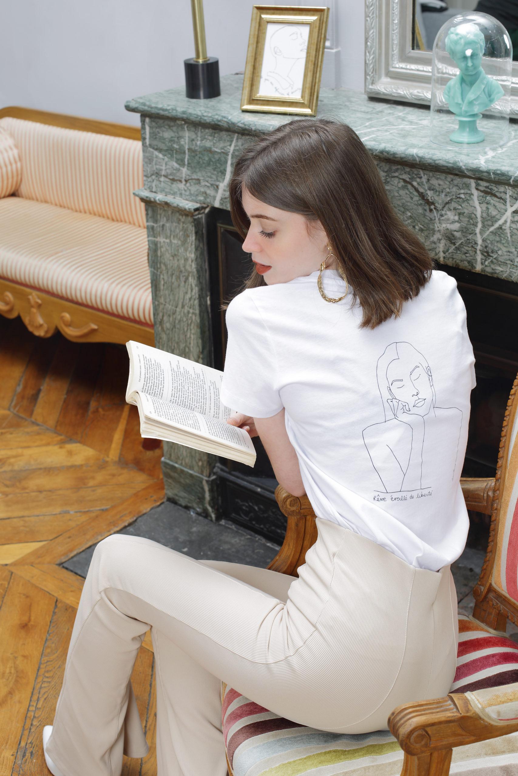 femme qui lit un livre, elle porte un tshirt blanc, le visuel est themis