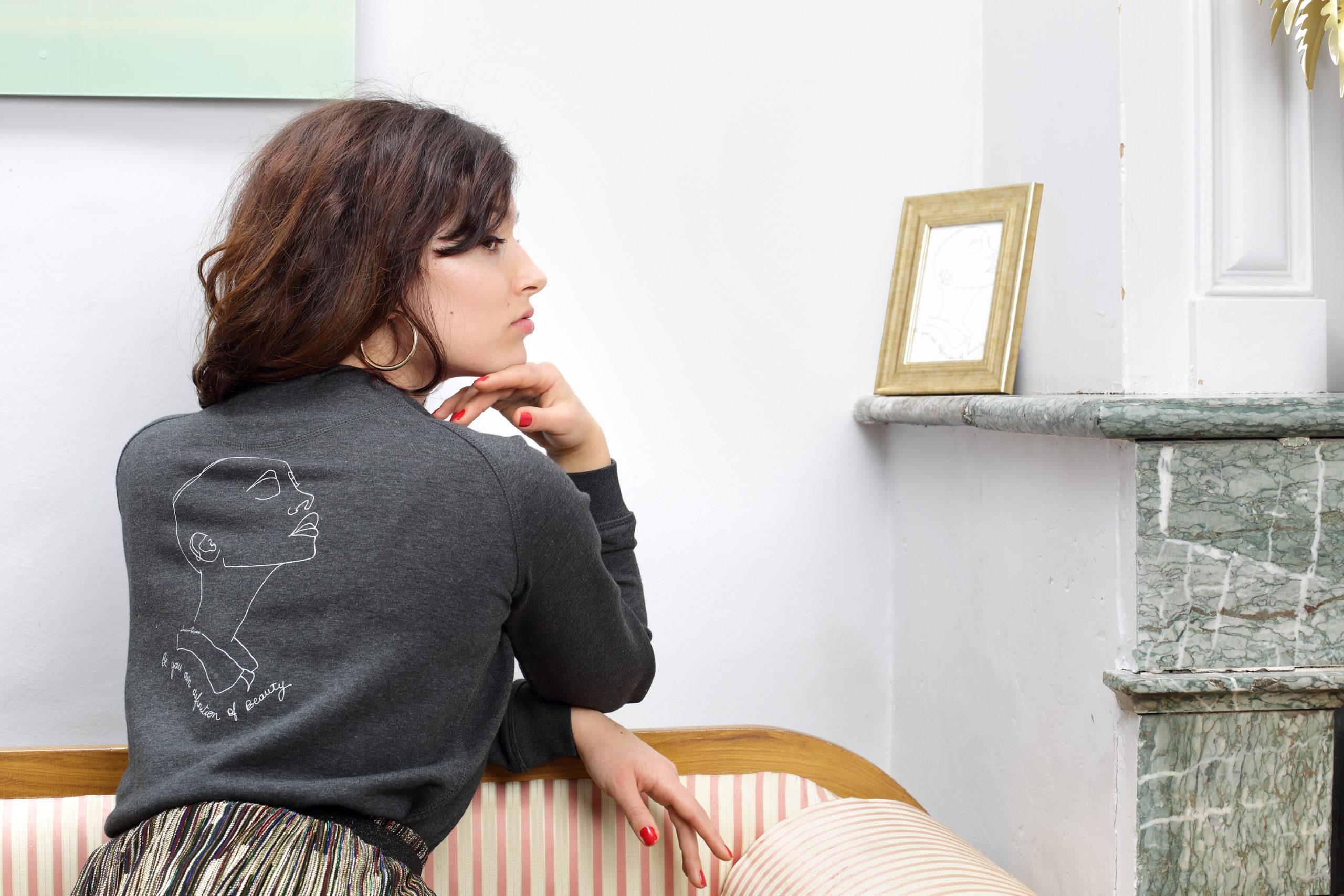 femme de dos portant un sweatshirt gris, avec comme visuel une représentation de la déesse sekhmet