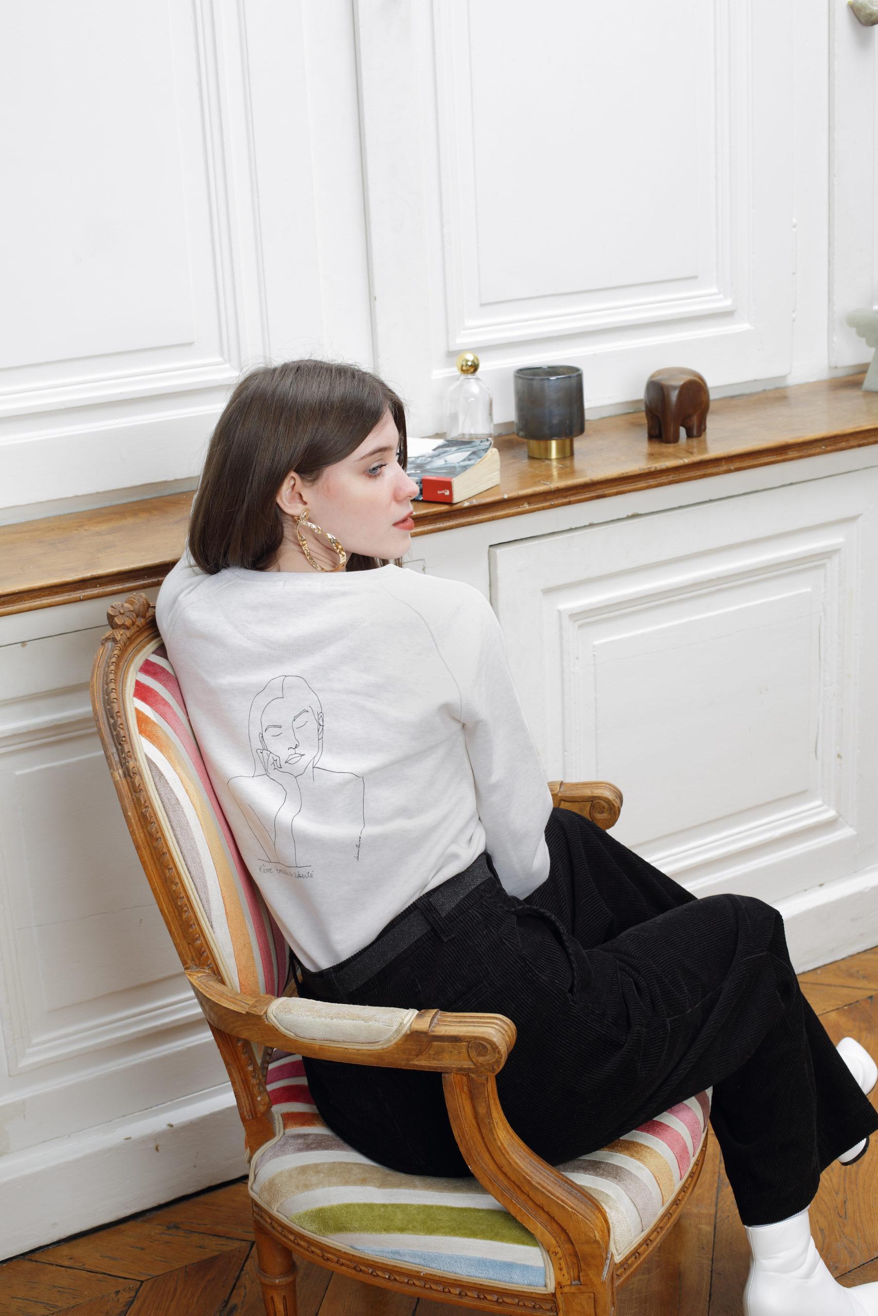 Femme portant un sweatshirt créme en coton bio de la marque leonor roversi