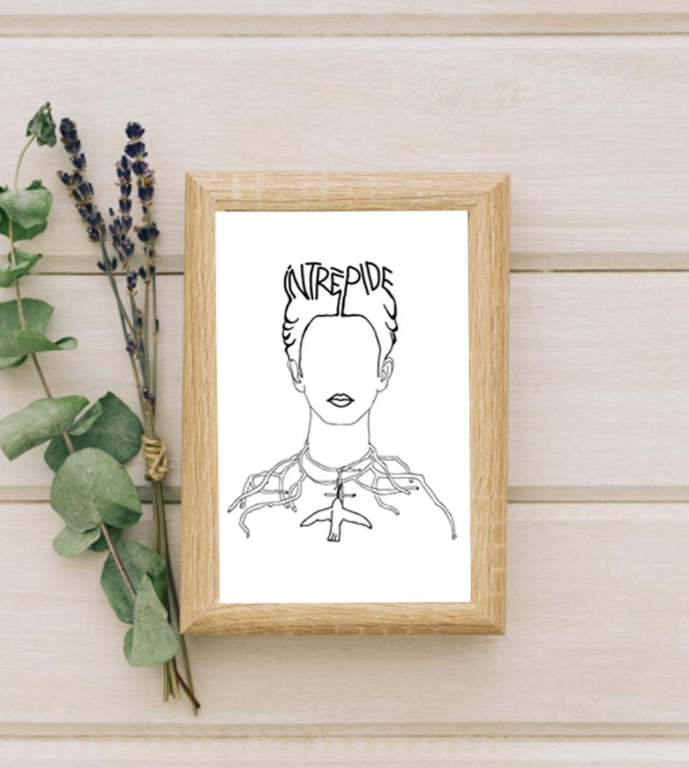 Image d'un cadre en bois avec une affiche A4 d'un visuel inspiré d'un tableau de Frida Kahlo à côté des eucalyptus