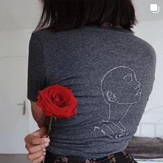 Femme de dos portant le t-shirt sekhmet gris avec une rose rouge