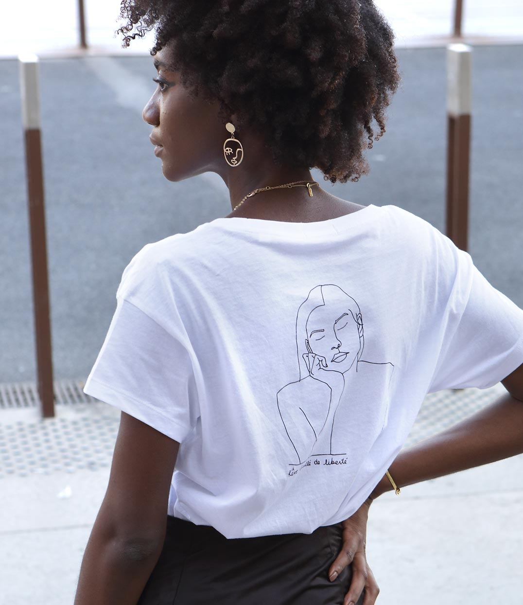 femme afro portant un tshirt blanc avec dessin de dos themis leonor roversi