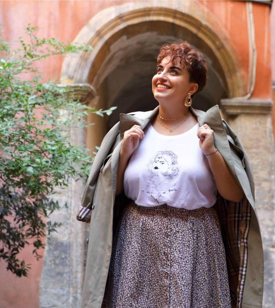 femme contente debout qui porte une jupe à fleur avec le t-shirt lupita de la nouvelle collection reinas de leonor roversi