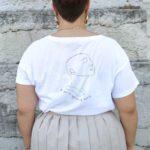 femme portant un t-shirt blanc avec le visuel représentant la déesse Sekhmet