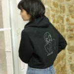 femme regardant par la fenêtre portant un sweat-shirt noire à capuche
