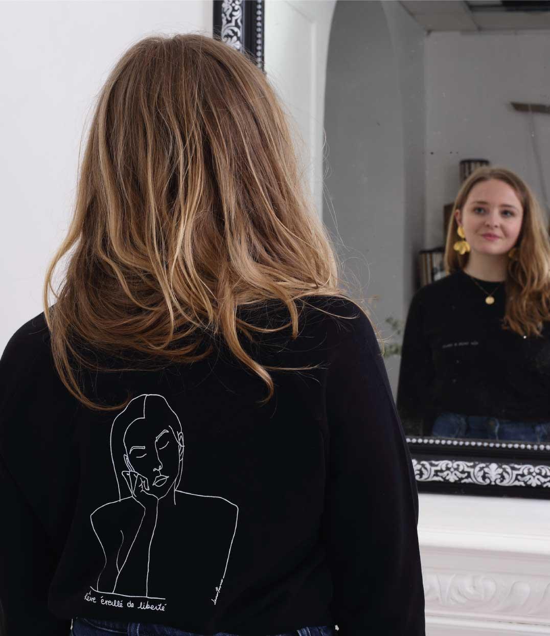 femme devant le miroir portant le sweatshirt themis noir de Leonor Roversi