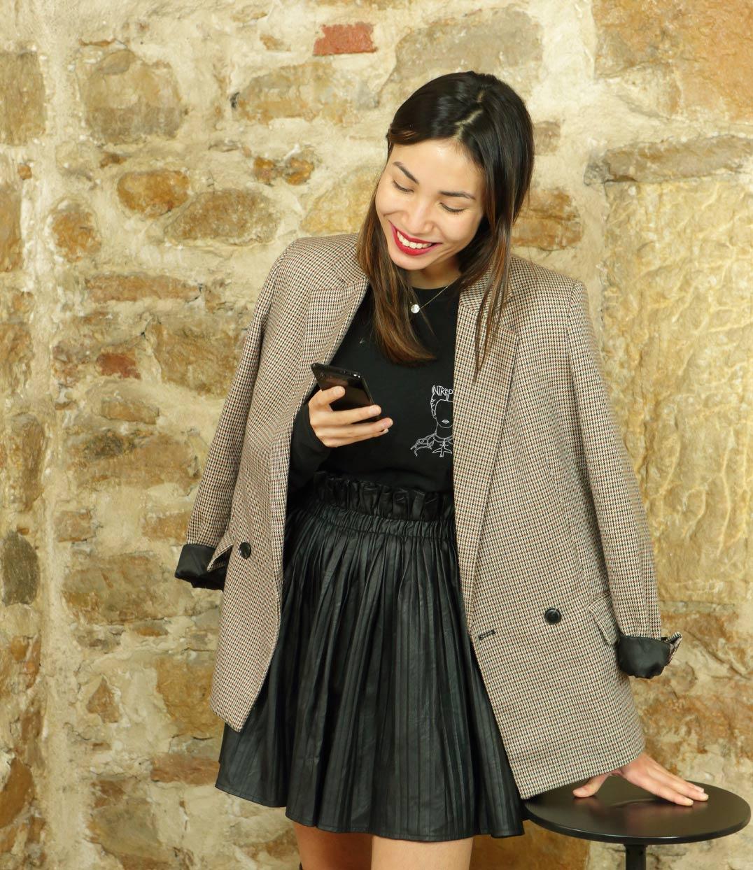 femme souriante regardant son telephone portant un tshirt noir leonor roversi