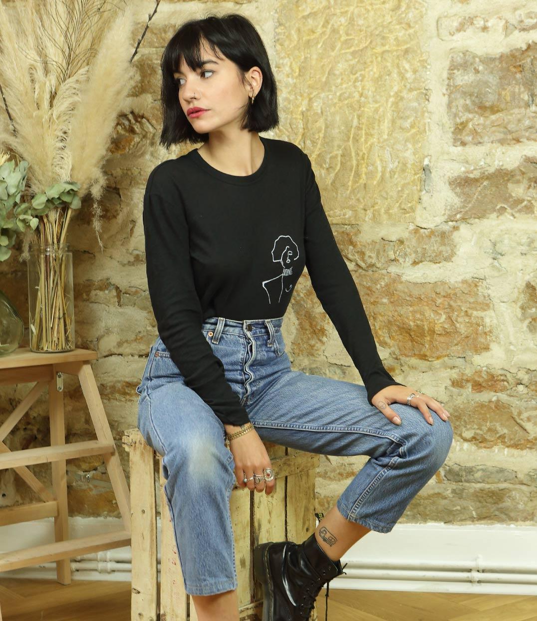 femme portant T-shirt manches longues noir assise sur un tabouret