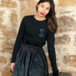 femme debout portant le tshirt manches longues frida noir de Leonor Roversi avec une jupe