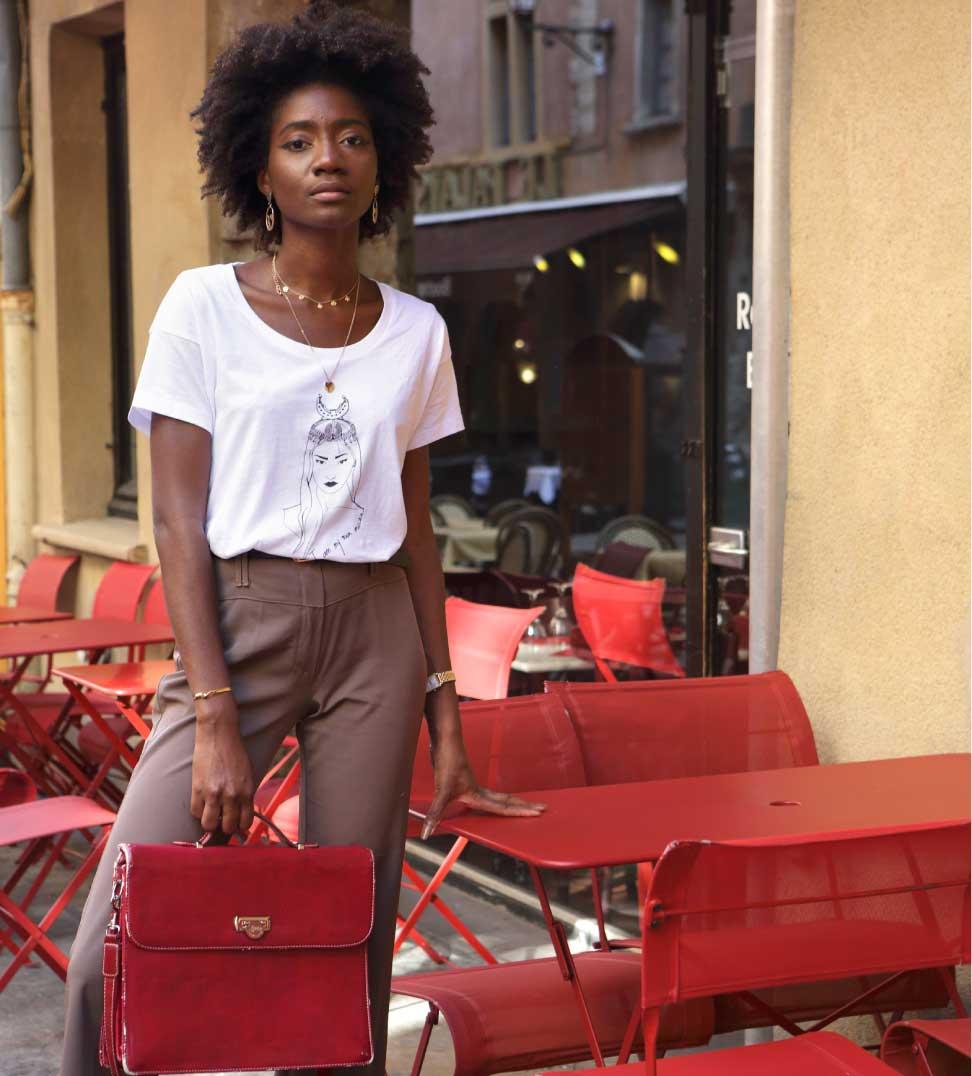 femme noire debout dans un café qui porte le t-shirt coyoqui