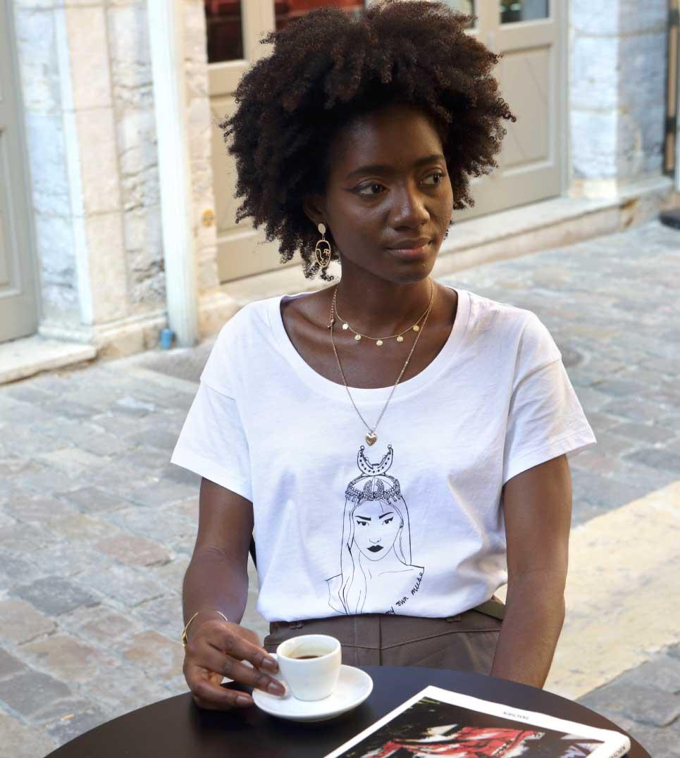 femme noire qui boit un café en terrasse avec le t-shirt coyoqui des reinas de Leonor Roversi