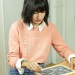 femme dessinant sur une ardoise portant un sweatshirt feministe leonor roversi