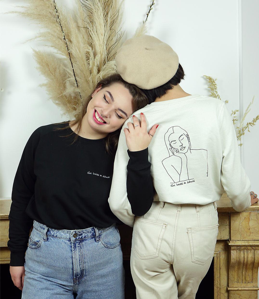 Deux femmes se tenant la main portant des sweatshirts dans la sororité