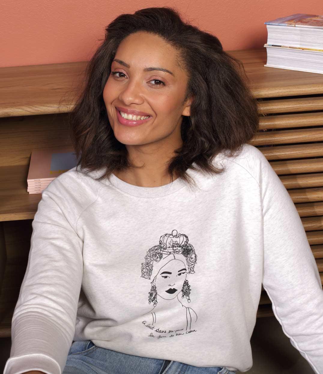 une femme porte le sweat crème esperanza leonor roversi. Elle est assise et sourie à l'objectif