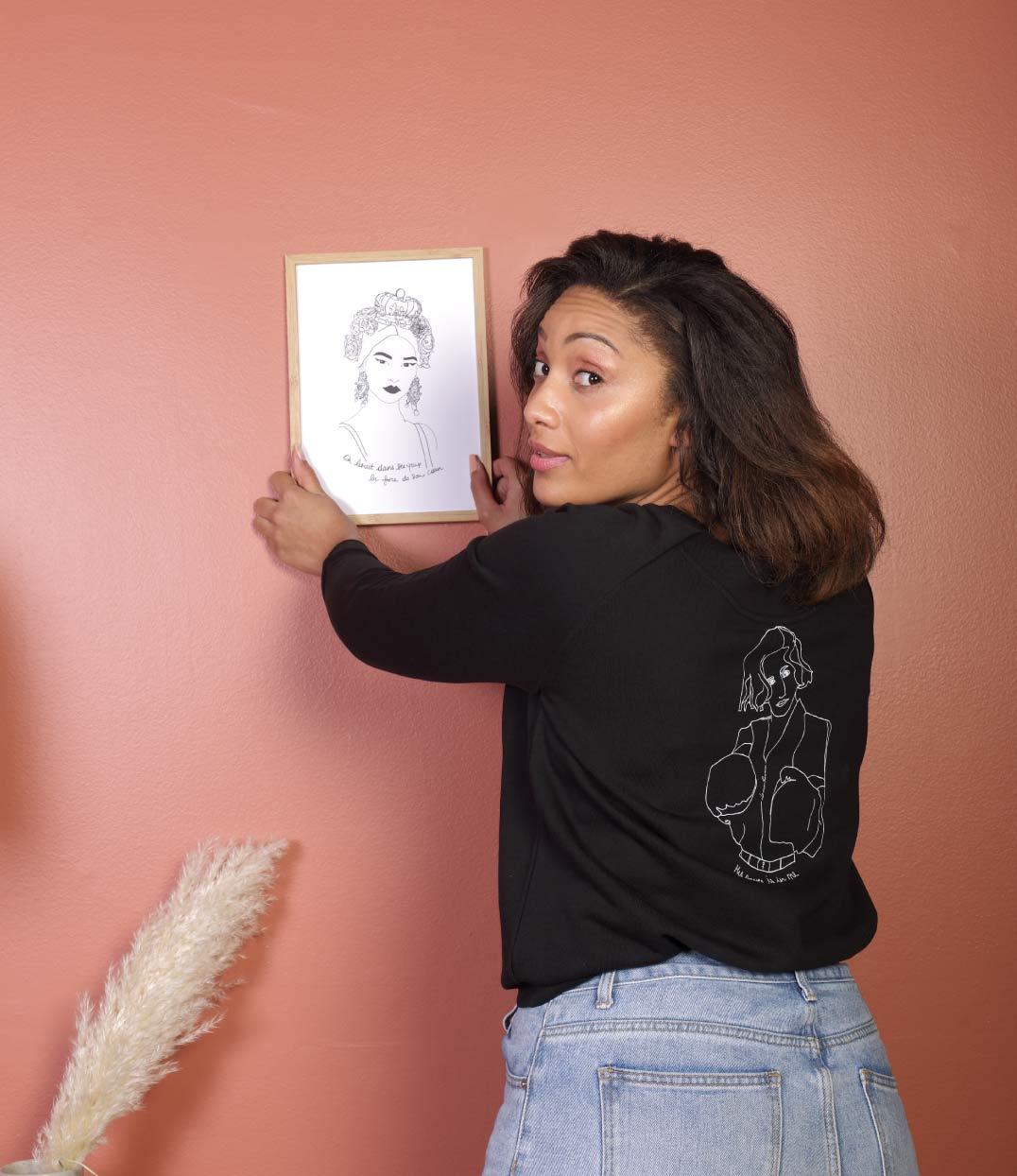 femme de dos dans le salon avec un sweat freyja noir leonor roversi tenant une affiche esperanza