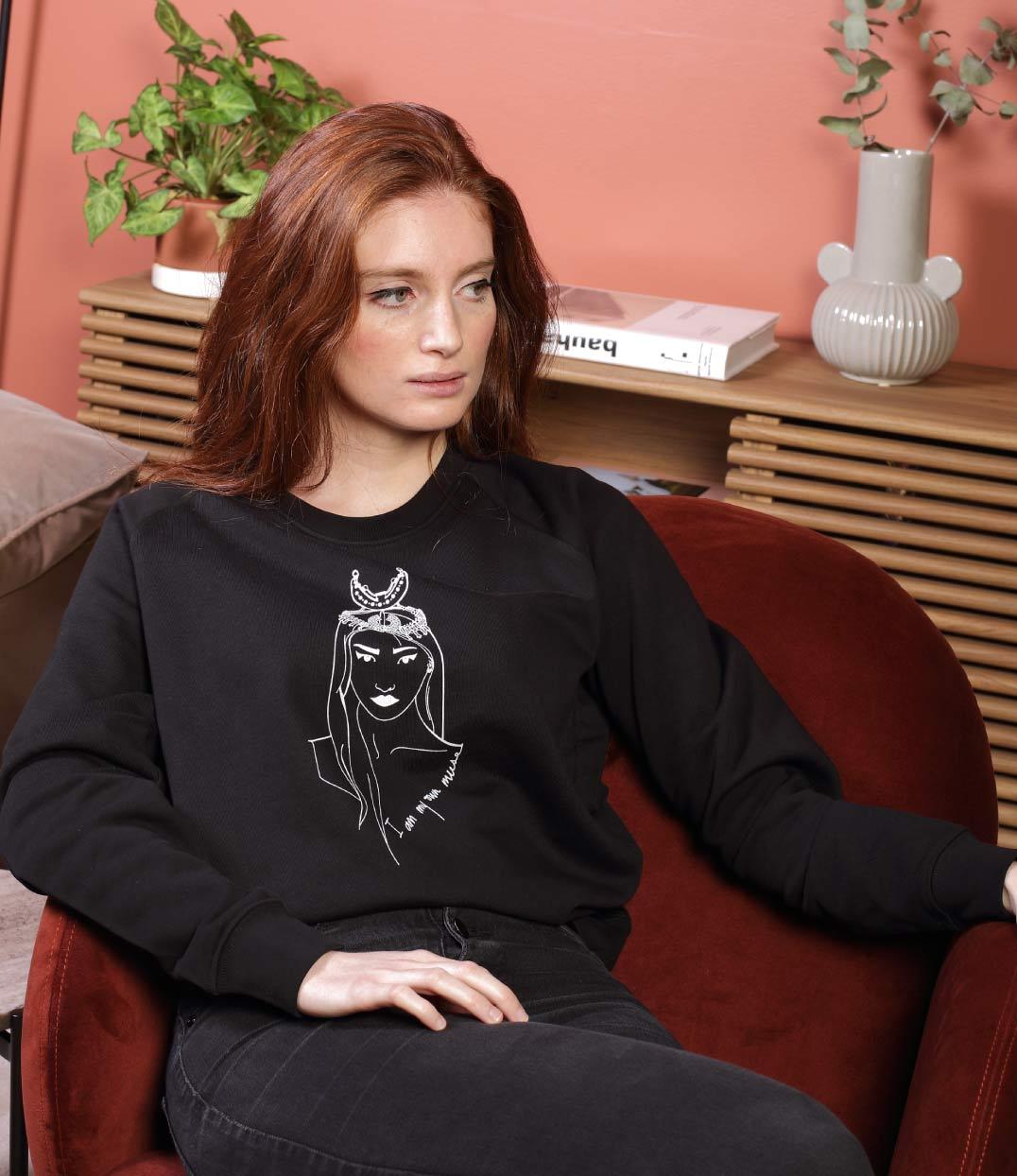 femme assise dans fauteuil qui porte un sweat coyoqui noir leonor roversi