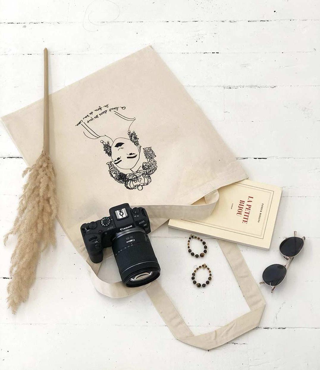 Un tote bag esperanza en coton leonor roversi est ouvert sur le sol. Il y a aussi un appareil photo et un livre