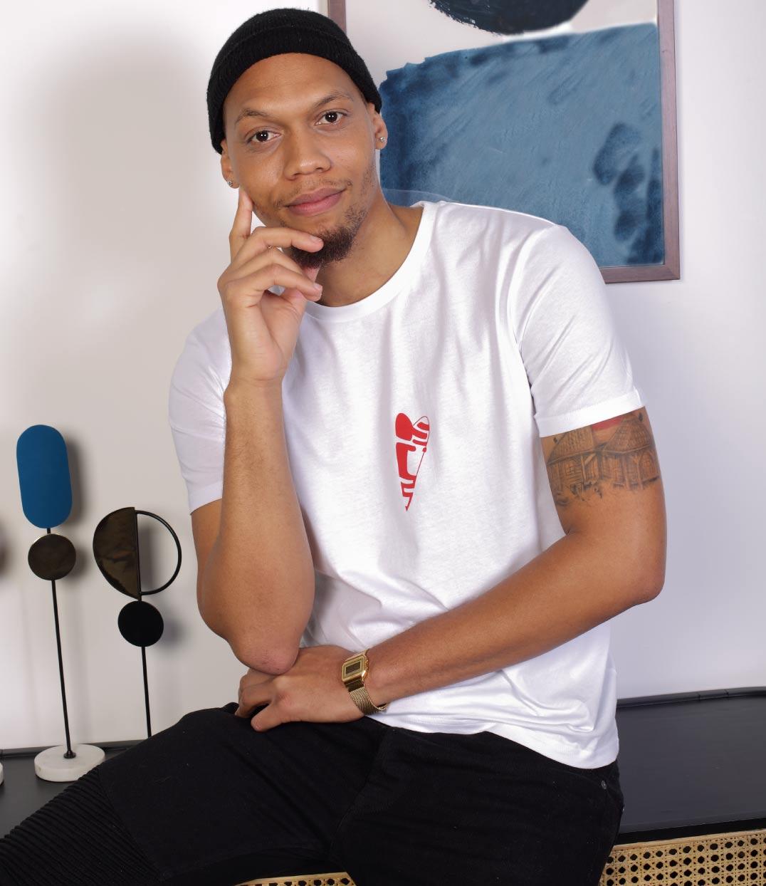 Un homme brun est assis sur un meuble. Il regarde devant lui et porte un jean noir ainsi qu'un tshirt blanc abracito en coton leonor roversi
