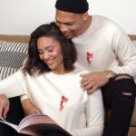 Un homme et une femme lisent un magazine en souriants. Ils portent tous les deux un sweat abracito leonor roversi
