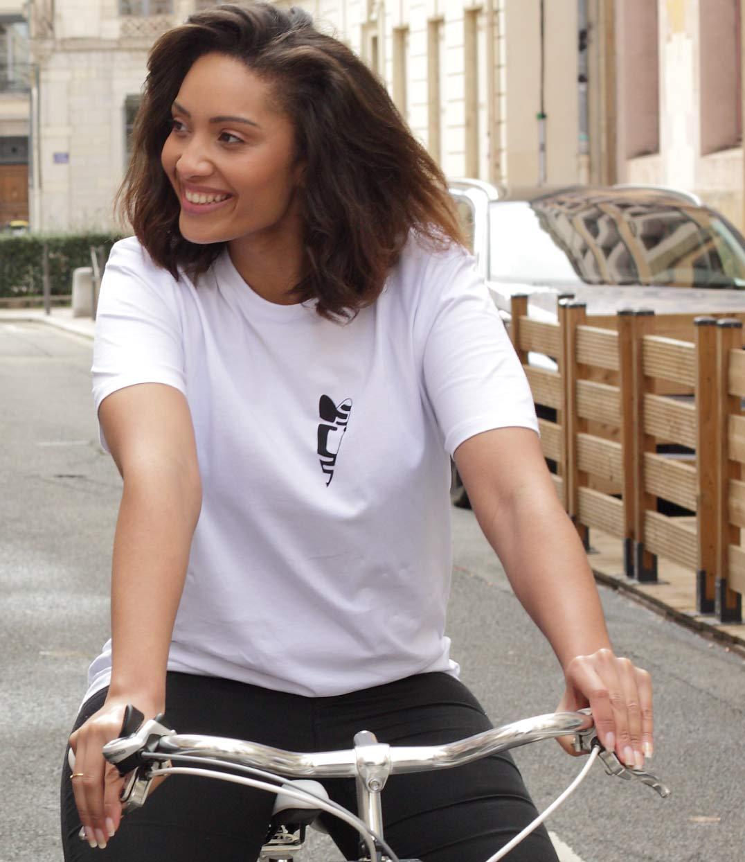 Une femme brune fait du vélo. Elle sourie et porte le tshirt abracito coeur noir en coton biologique leonor roversi