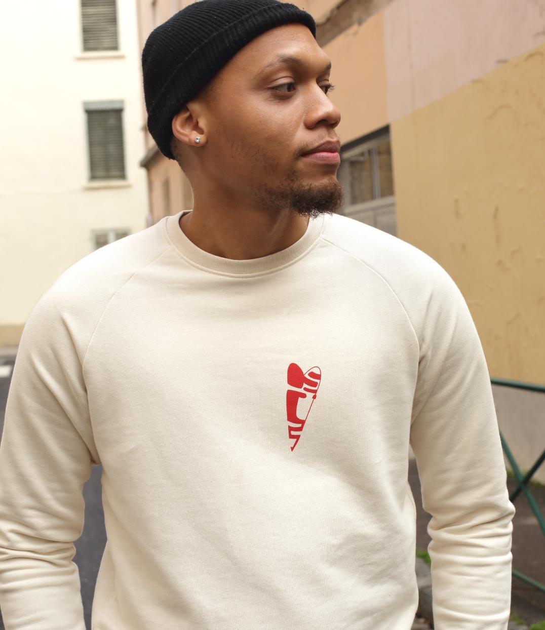 Un homme est dans la rue. Il porte le sweatshirt beige abracito coeur rouge leonor roversi