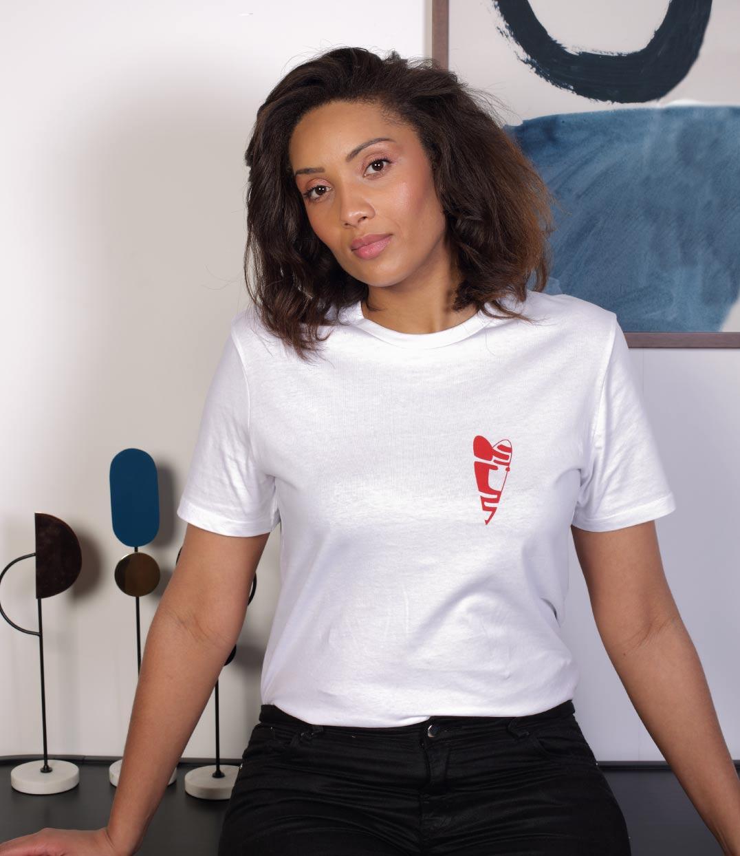 Une femme brune regarde devant elle. Elle porte un tshirt blanc abracito coupe unisexe leonor roversi