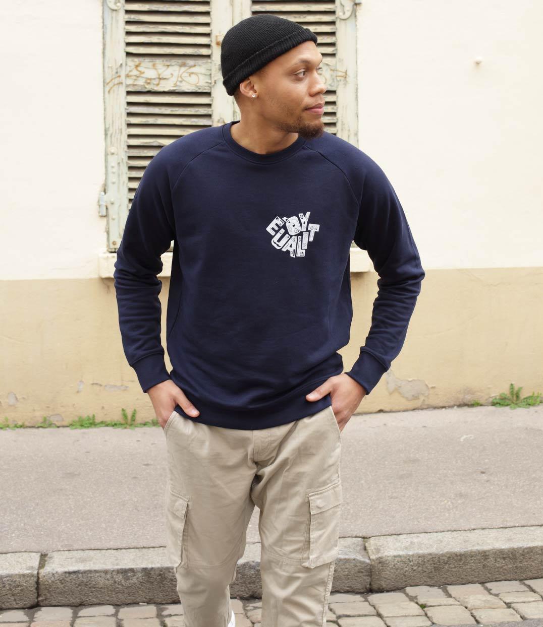 Un homme est dans la rue. Il regarde au loin et porte le sweatshirt equality bleu leonor roversi