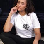 Une femme brune porte un t-shirt blanc equality assise au sol d'un salon adossée à un canapé bleu