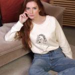 Une femme rousse porte un sweat Lupita beige leonor roversi. Elle est assise et regarde l'objectif.