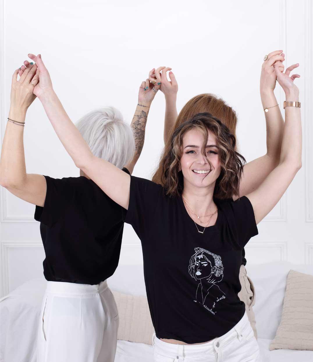 Trois femmes dansent main dans la main et dos à dos. L'une des femmes regarde vers la caméra, tandis que les autres ont le dos. Elles portent des t-shirts noirs Leonor Roversi
