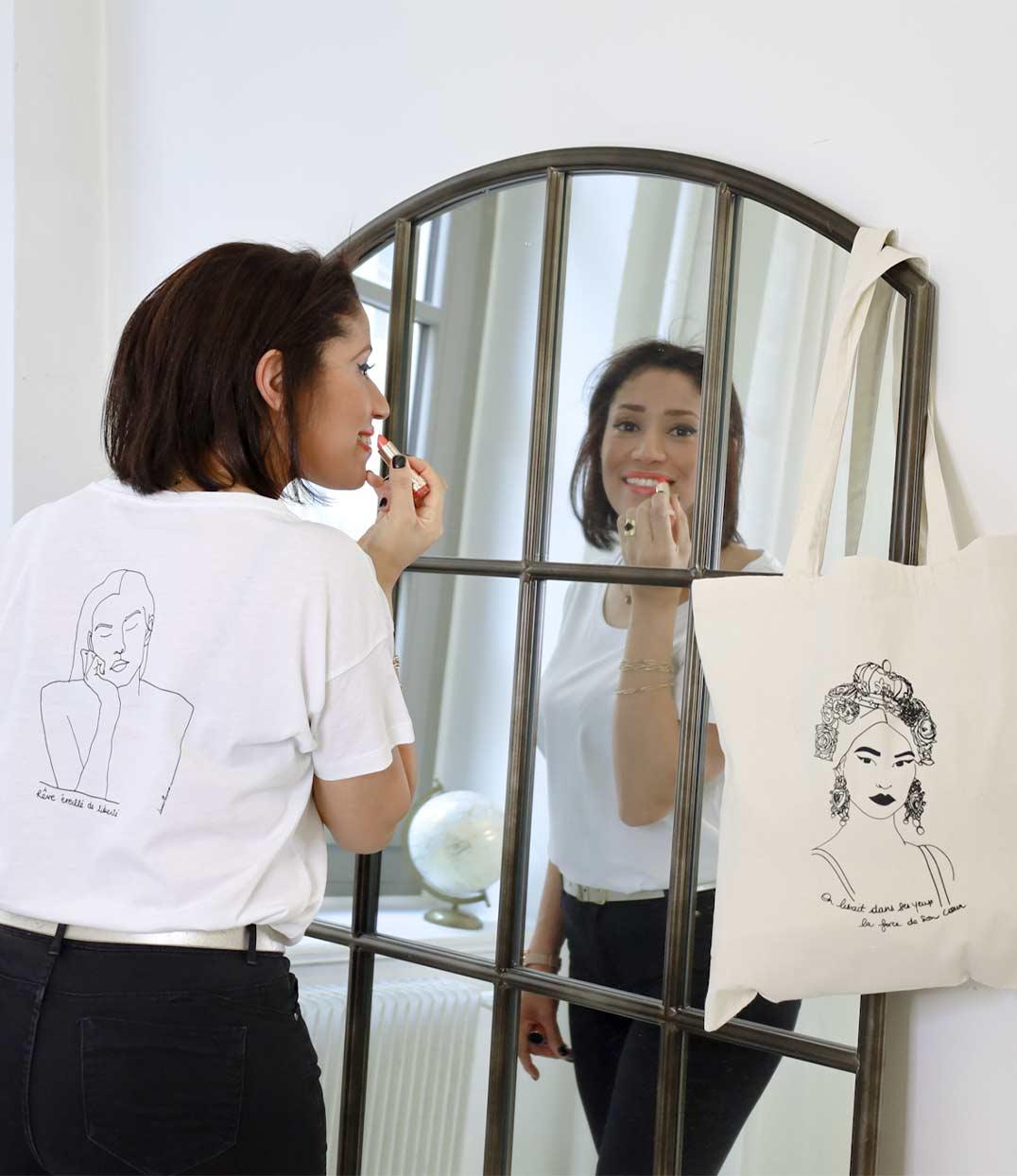 femme devant le miroir portant le tshirt themis blanc loose de Leonor Roversi à coté d'un tote bag esperanza accroché