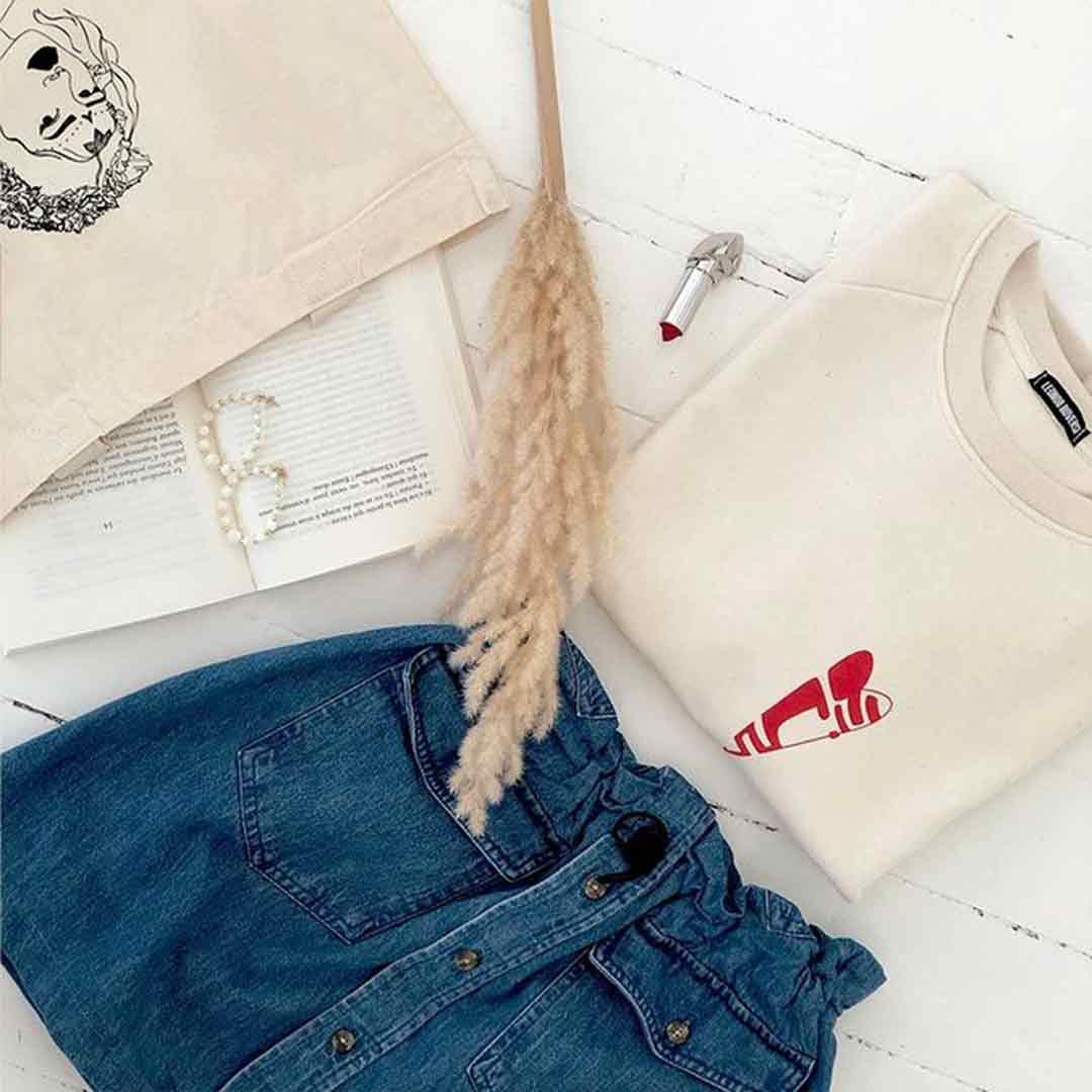 tote bag lupita et sweathirt abracito Leonor Roversi posés sur une table avec une jupe en jean