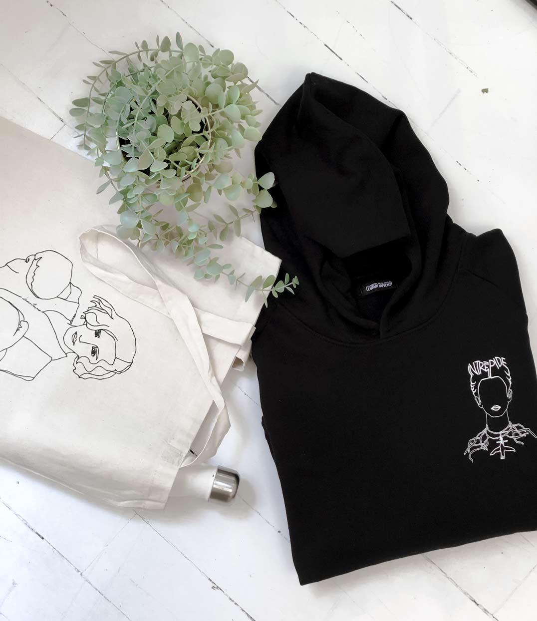 Sweatshirt frida noir Leonor Roversi plié posé sur une table et tote bag freyja