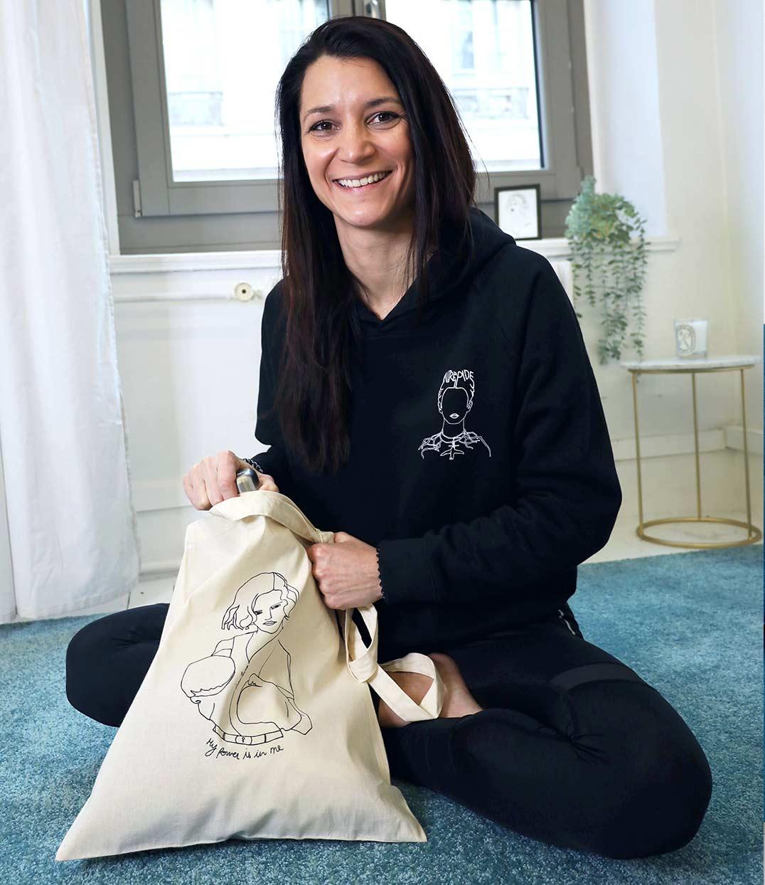 Femme assise portant le sweatshirt frida avec un tote bag freyja Leonor Roversi