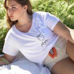 jeune femme qui porte un t-shirt blanc loose frida en coton de la marque leonor roversi allongée dans l'herbe