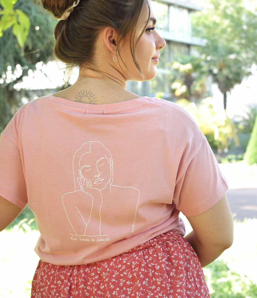 jeune femme qui porte un t-shirt rose thémis de la marque leonor roversi